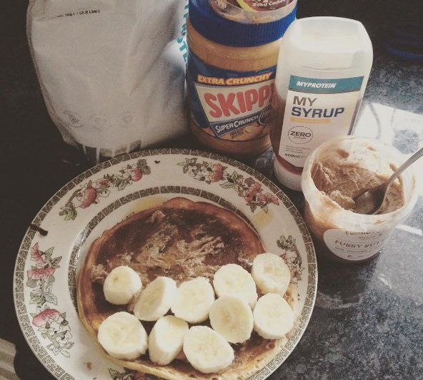 protein pancakes on plate with ingredients in the background and bananas on the pancakes