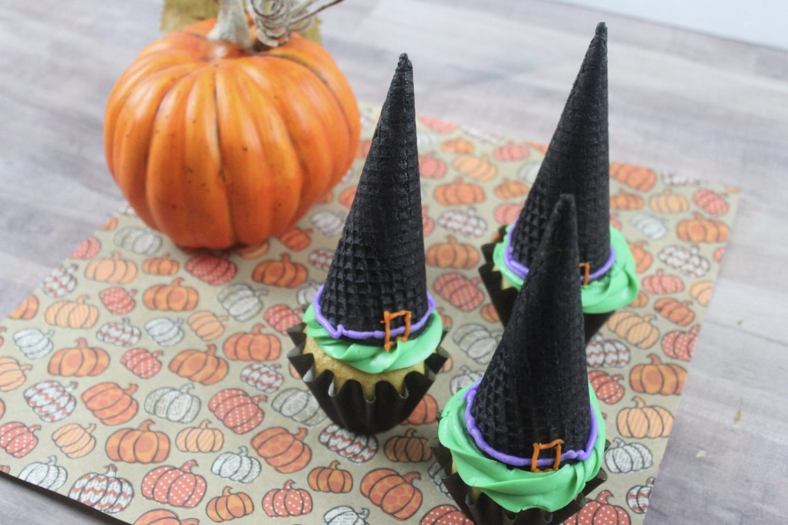 witch hat cupcakes on pumpkin printed napkin with small pumkpin in background