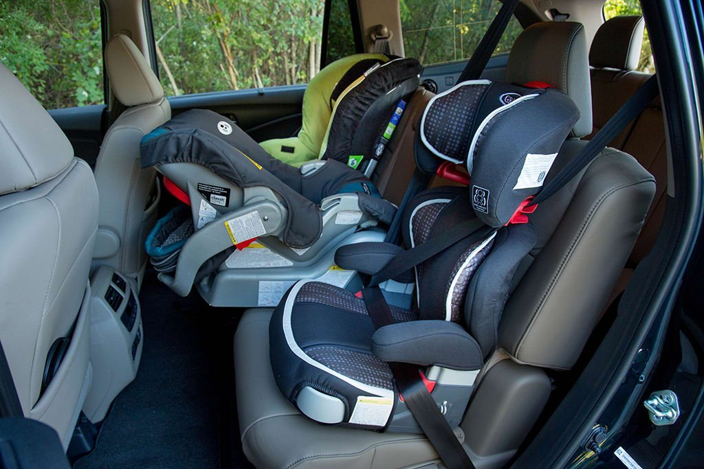 row of children's car seats in back of family car