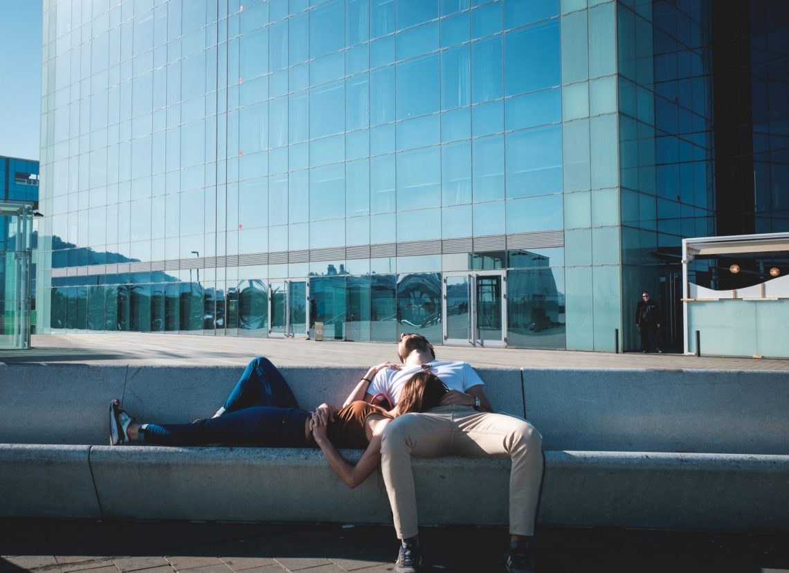 couple sleeping in new york sitting on a long stone bench with the woman resting her head in man's lap with glossy skyscraper background and blue sky
