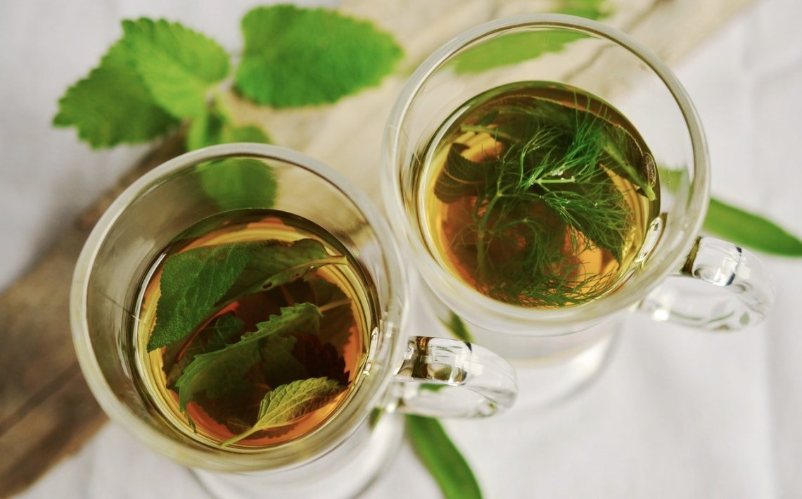 herbal tea in two glasses next to each other on a white background.