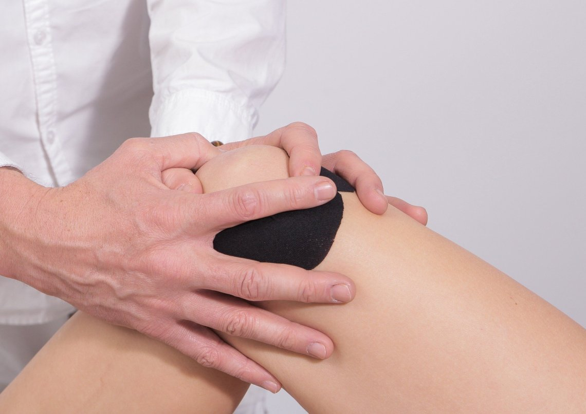 strapped knee with someone holding their fingers around the knee joint