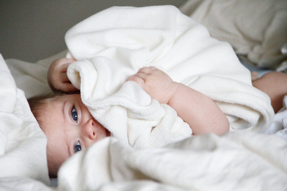 cute baby hiding under a blanket how to suppress breast milk feature image