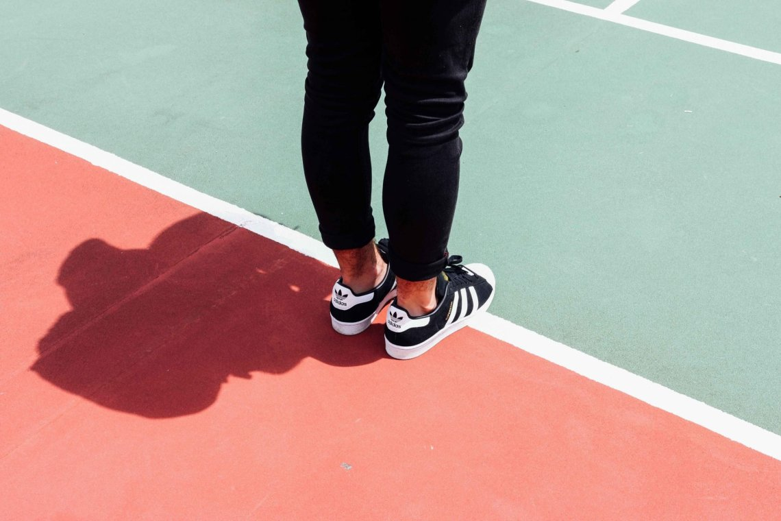 Adidas trainers close up on a tennis court