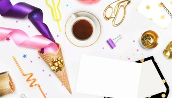 white background with party supplies and notebook on