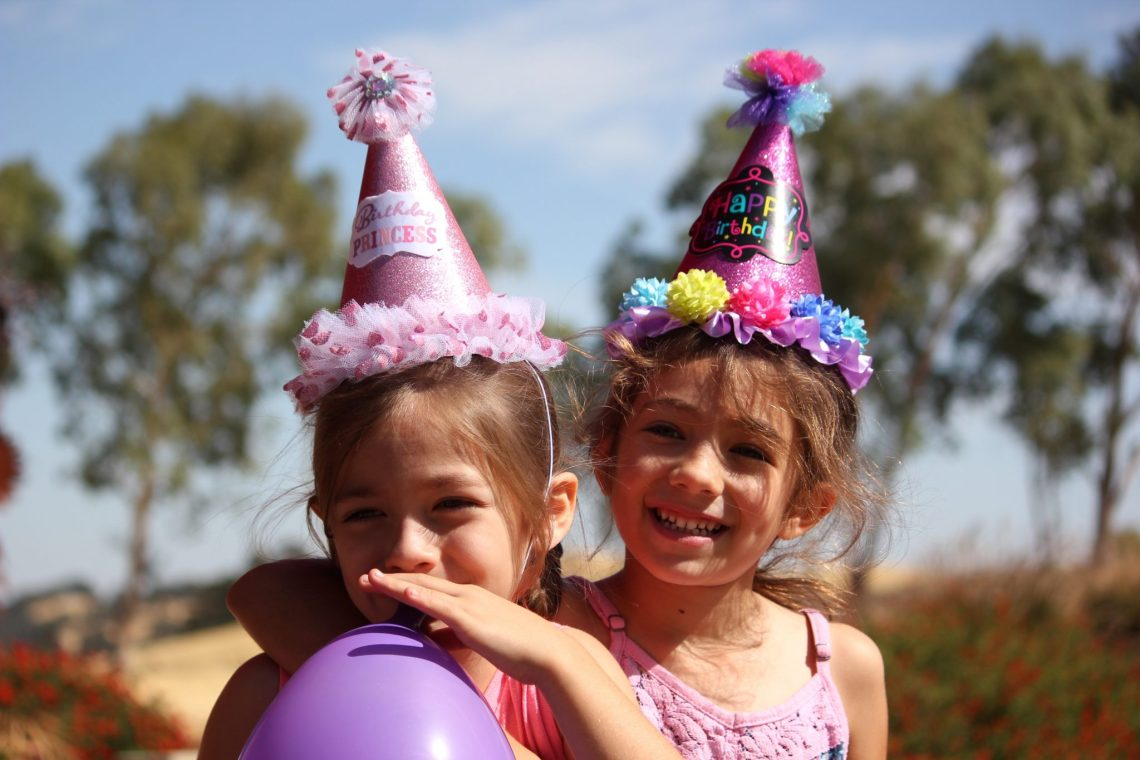 two girls in party hats one blowing up a purple balloon, outside in the sun