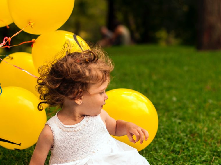Little girl in white dress on grass background next to bunch of yellow balloons