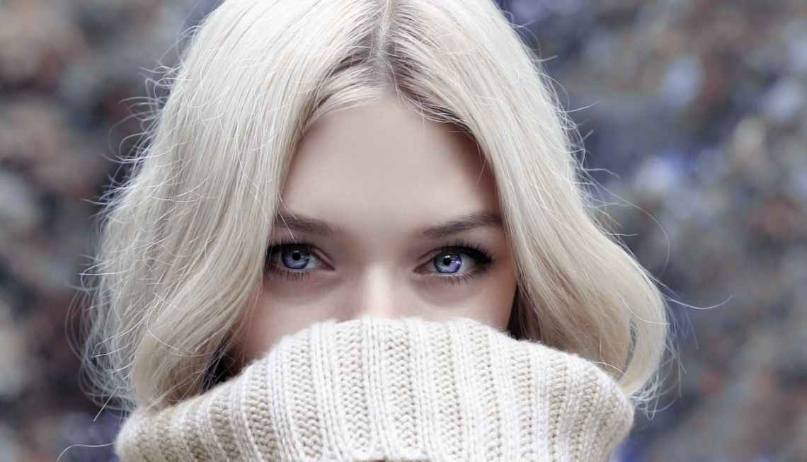 blonde woman hiding her face in her jumper, just showing blue eyes at the screen