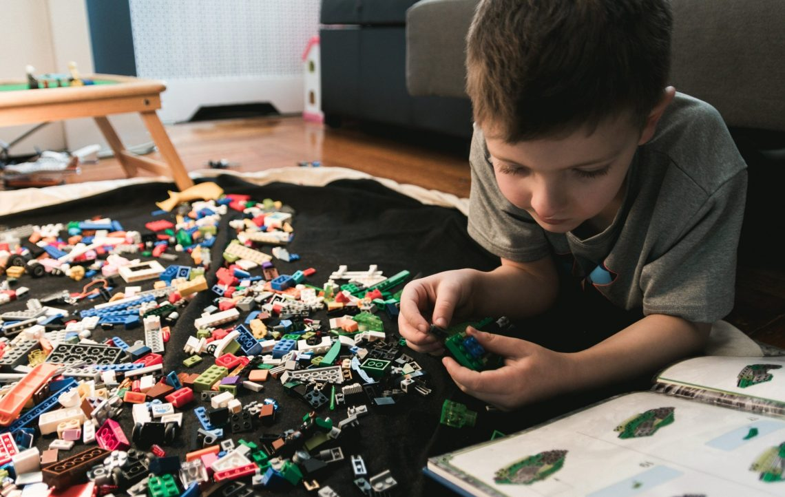 boy playing lego on the floor