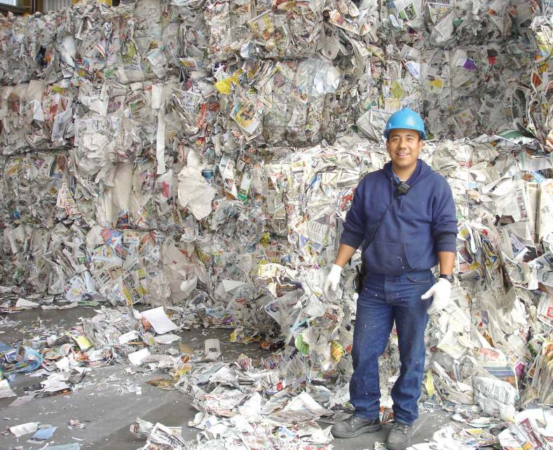 An employee at Boulder County Recycling Center, in Colorado, stands in front of piles of paper ready to be recycled.