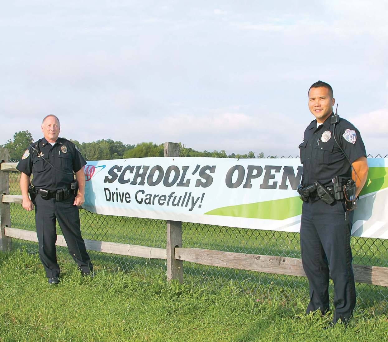 Hartinger, left, and a fellow Blue Ash Police Department officer remind drivers to watch for students as area schools go back into session. (Photo provided)