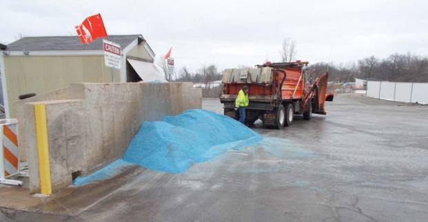 A McHenry County driver empties his remaining salt into a conveyor pit following a snow event. (Provided by APWA Winter Maintenance Technical Committee)