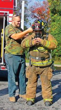 A Cheat Lake volunteer firefighter shows students his equipment as part of a demonstration for preschool children. Funds received from the firework sales tax can be used not only toward training supplies, but fire prevention promotional materials up to a certain dollar amount. (Photo provided)