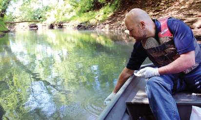 Matt Powell, city of Bowling Green, Ky., environmental manager, collects water samples to test from Jennings Creek. At one station there is now continuous monitoring when previously there had only been quarterly sampling. (Photo by Laura Harris)