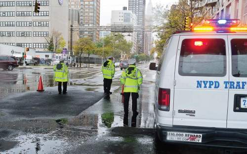 To ensure first responder transportation needs are met, fleet services managers need a playbook that covers every potential scenario and also encourage workers to have personal playbooks for their home so they can focus on the work at hand. Pictured are NYPD traffic officers prior to Hurricane Sandy's arrival. (Shutterstock.com)