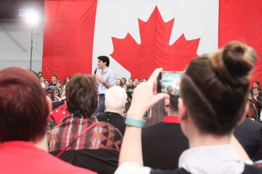 Large Canadian flag hangs in background. Justin Trudeau stands in front of flag while speaking into microphone. Backs of heads of out-of-focus crowd members, with one onlooker taking a picture of the scene on her phone is in foreground.