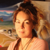 Woman with red-tinted hair and light brown eyes looks into the camera. An out-of-focus painting of two birds and a mountain landscape hangs in the background.