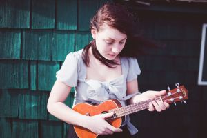 A girl with long brown hair wearing a pale purple blouse stands in front of a shingled wall, playing her ukulele