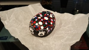 A painted ladybug rock sits on a piece of crinkled paper.