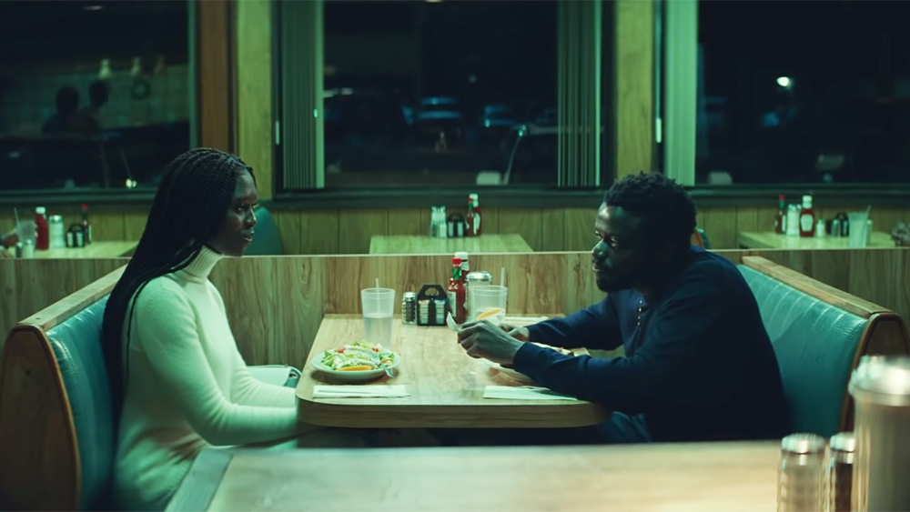 Two people sit at a booth in a diner