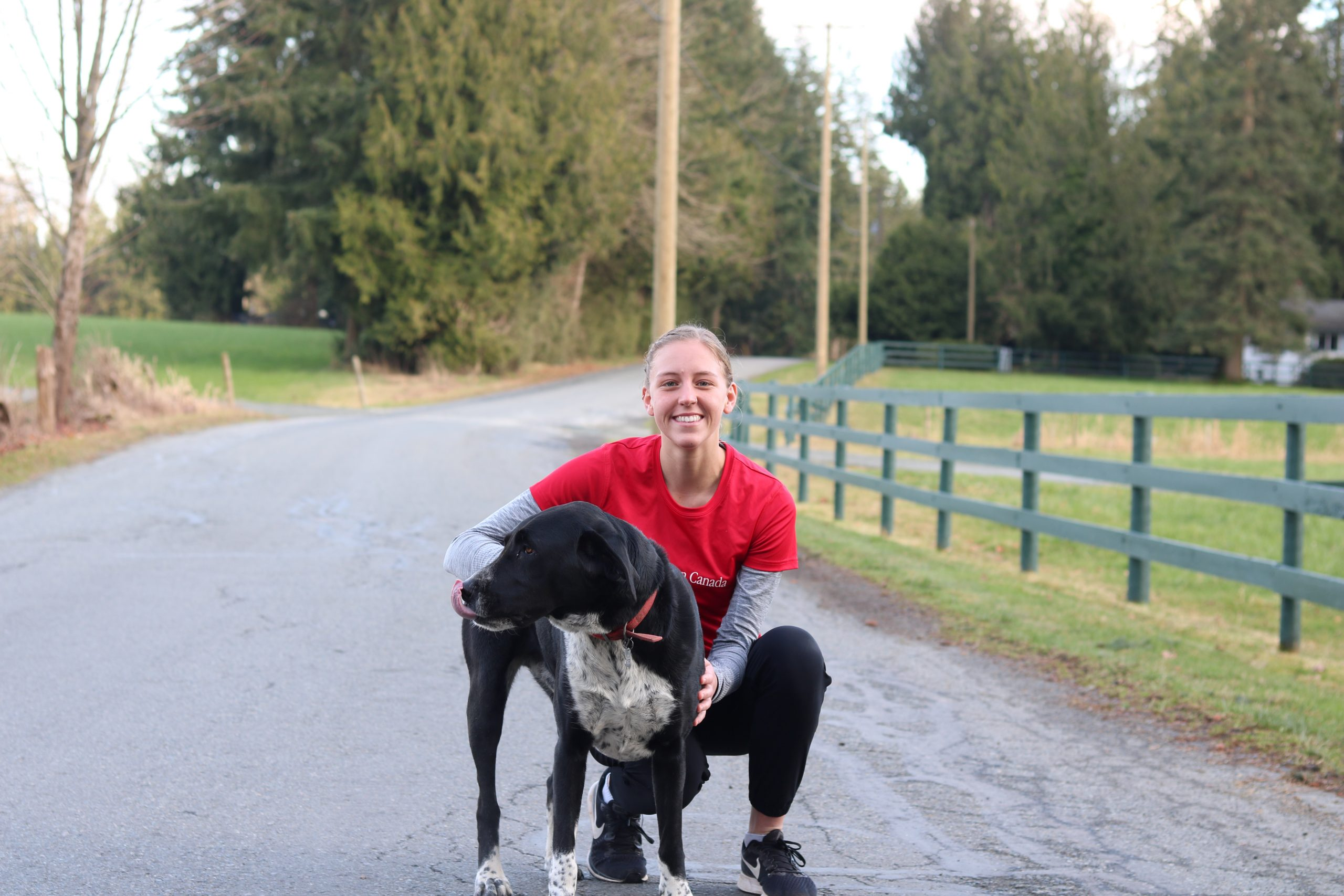 Danielle Groenedijk wearing balck leggings and a red shirt reading 'Parkinson Canada' crouched down on the road beside a grassy field to put her arms around her medium height, black and white dog, Bo
