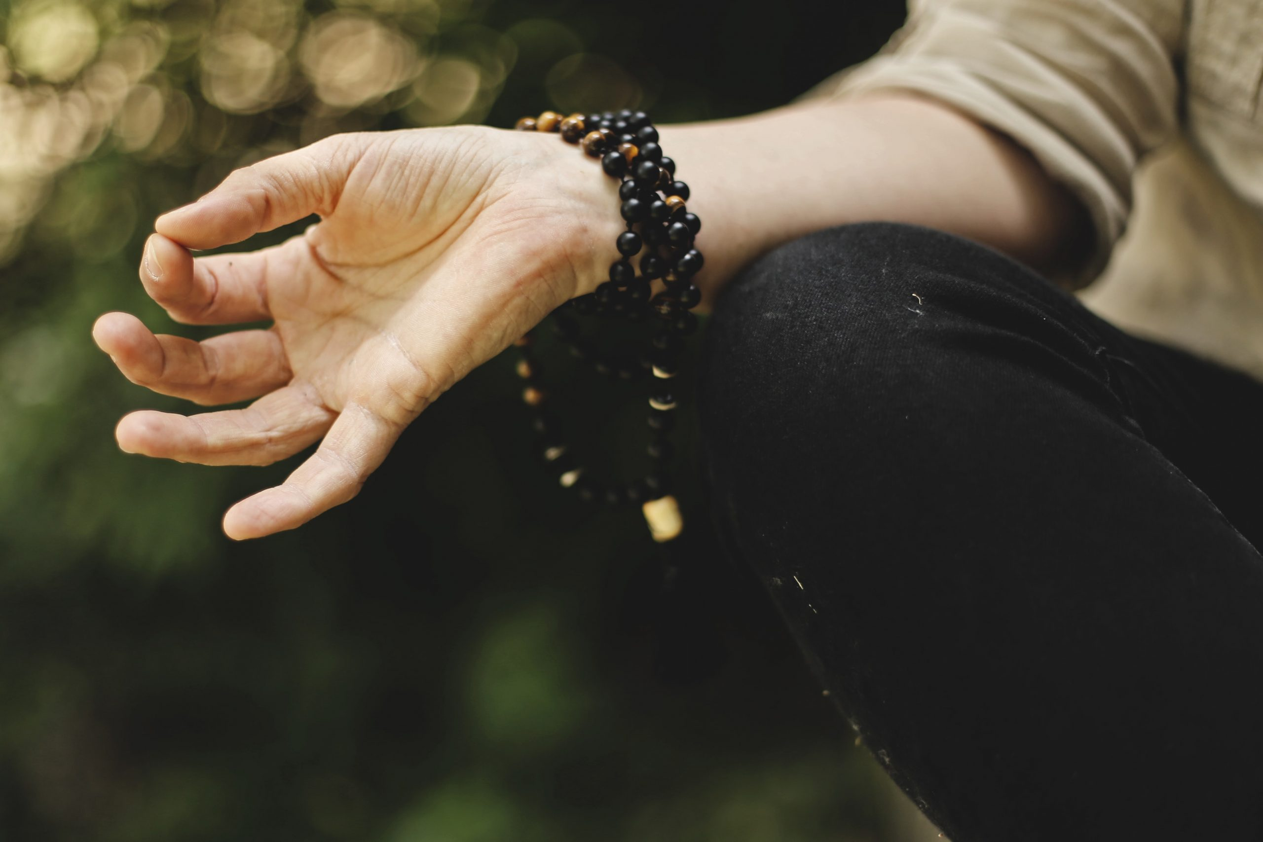 Hand with a brown beaded bracelet in meditative position.
