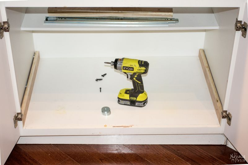 impact driver sitting in an empty cabinet with drawer slides