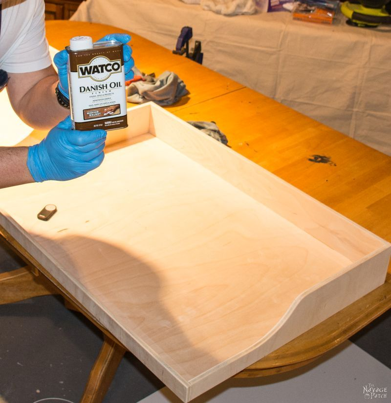 man holding can of danish oil