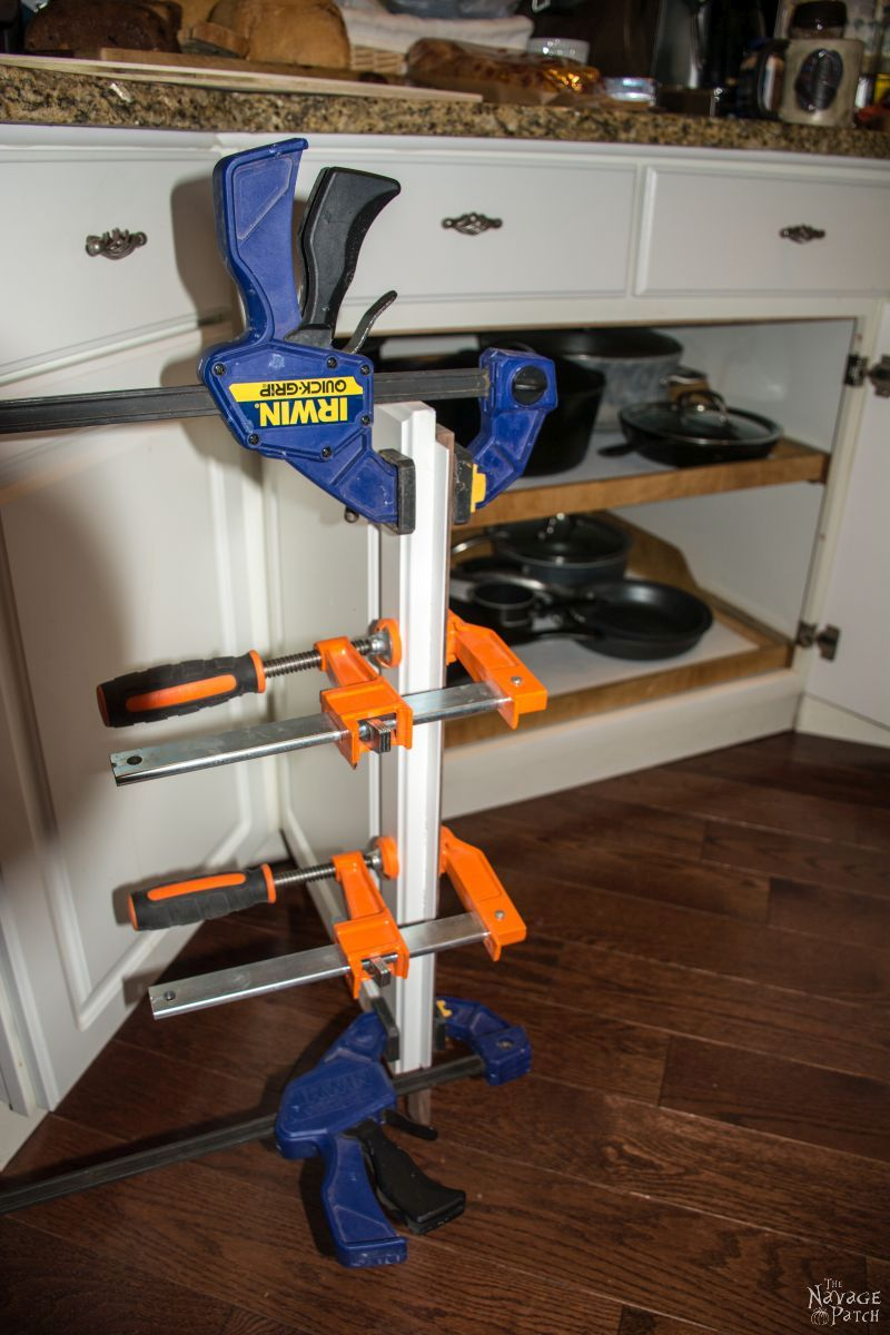 clamps holding a piece of polywall against a cabinet door