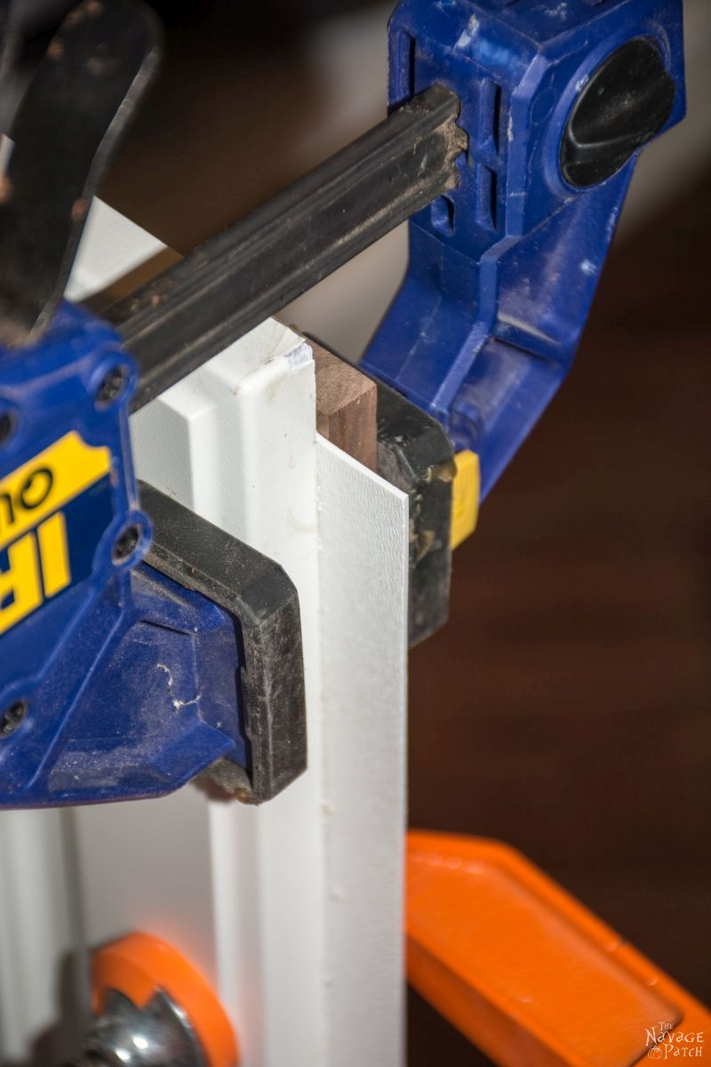 closeup of clamp holding polywall against a cabinet door