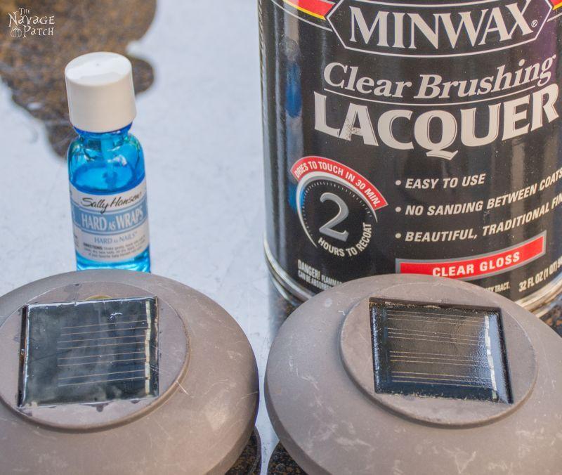 can of lacquer and bottle of clear nail polish behind to solar panels