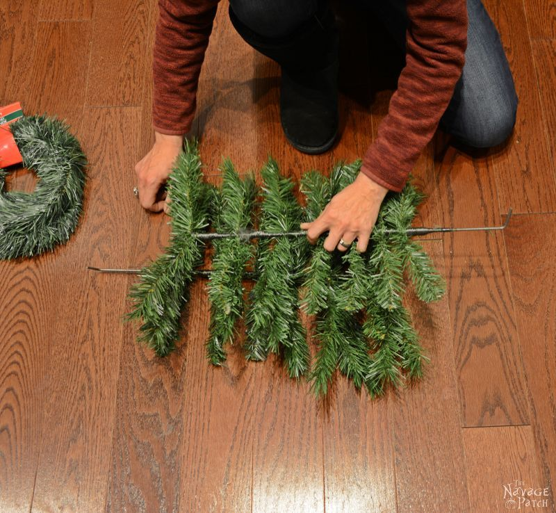 woman placing a fake christmas tree branch on top of another