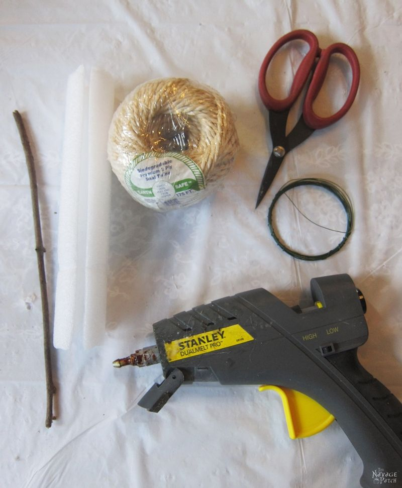 twine, scissors, glue gun, stick and wire on a table