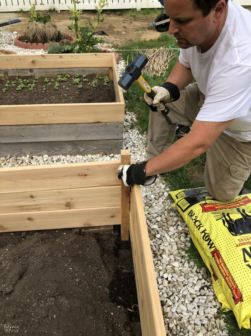 how to build a raised garden bed - man hammering in support stake