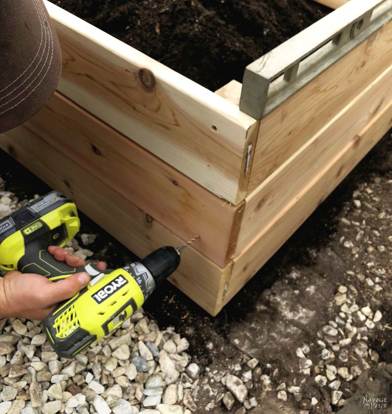 man showing how to build a raised garden bed -screwing the frame together