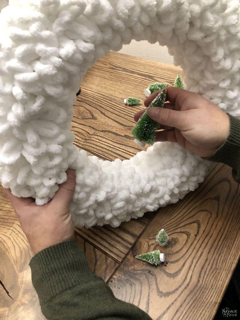man placing bristle brush trees in winter loop yarn wreath