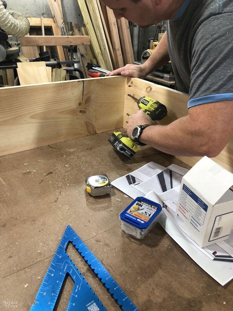 man screwing together daybed frame with pocket screws