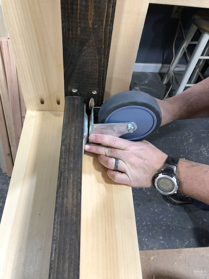 man attaching a caster to a diy daybed