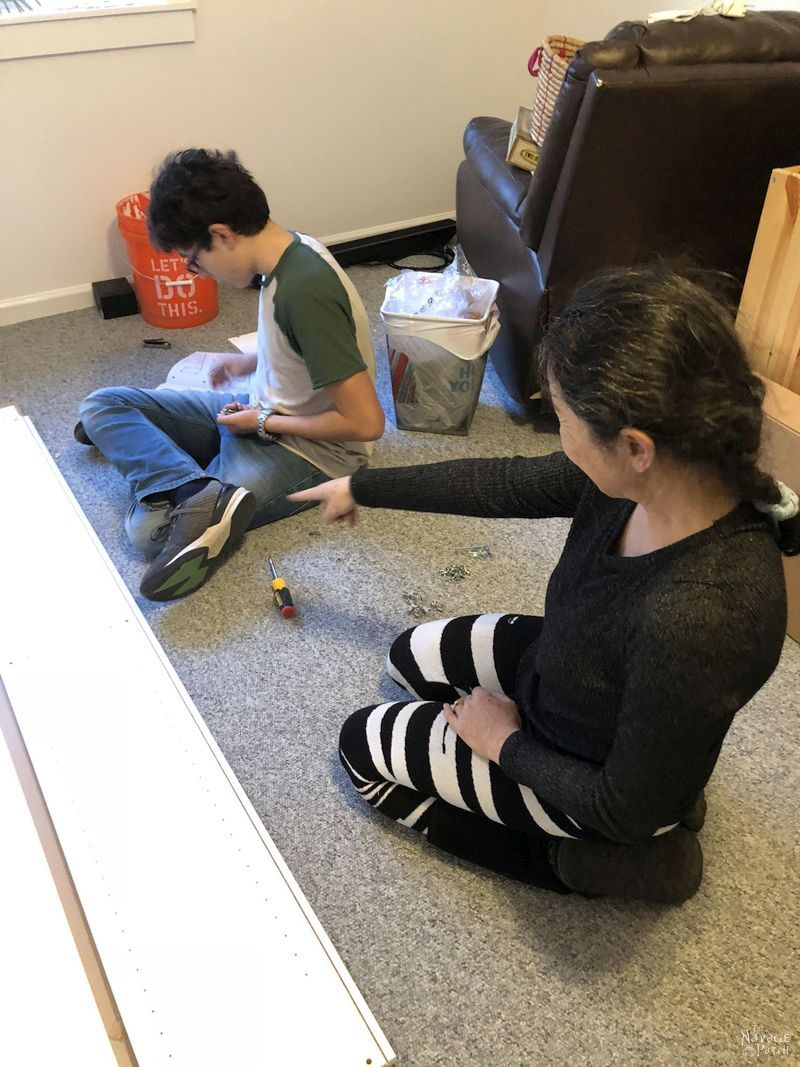 mother and son build IKEA furniture on the floor