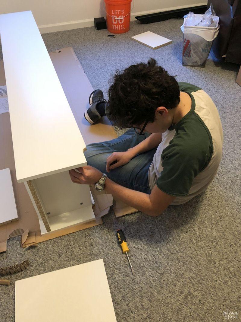 boy building an Ikea Billy bookcase