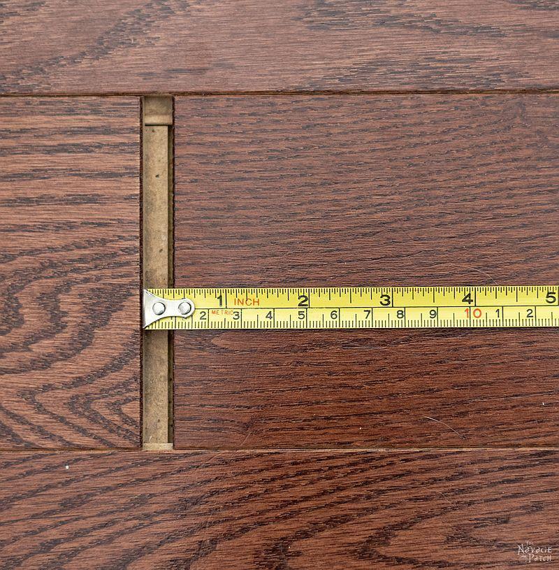 tape measure in a gap between floor boards