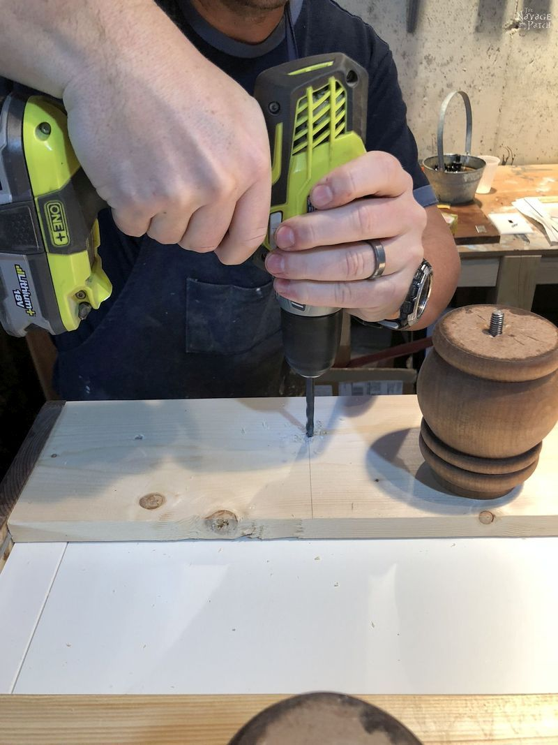 man drilling a hole in a board