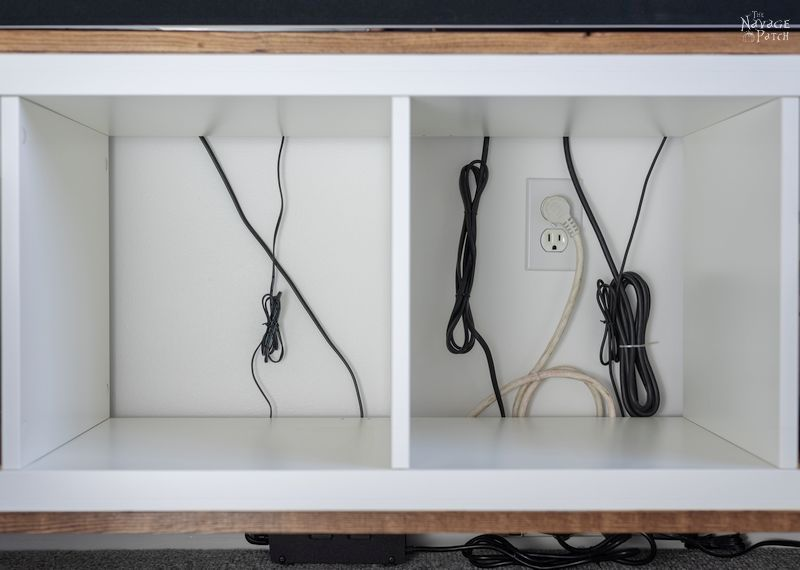 cords and cables at the back of an ikea kallax tv stand