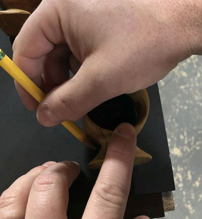 man with pencil marking plywood next to a napkin ring