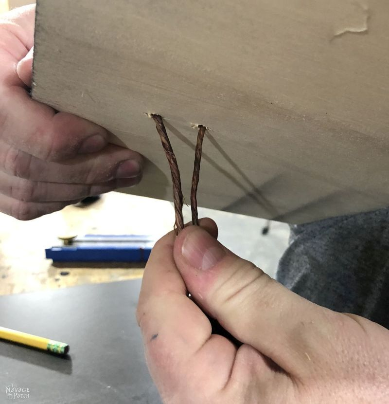 man pulling craft wire through holes in plywood