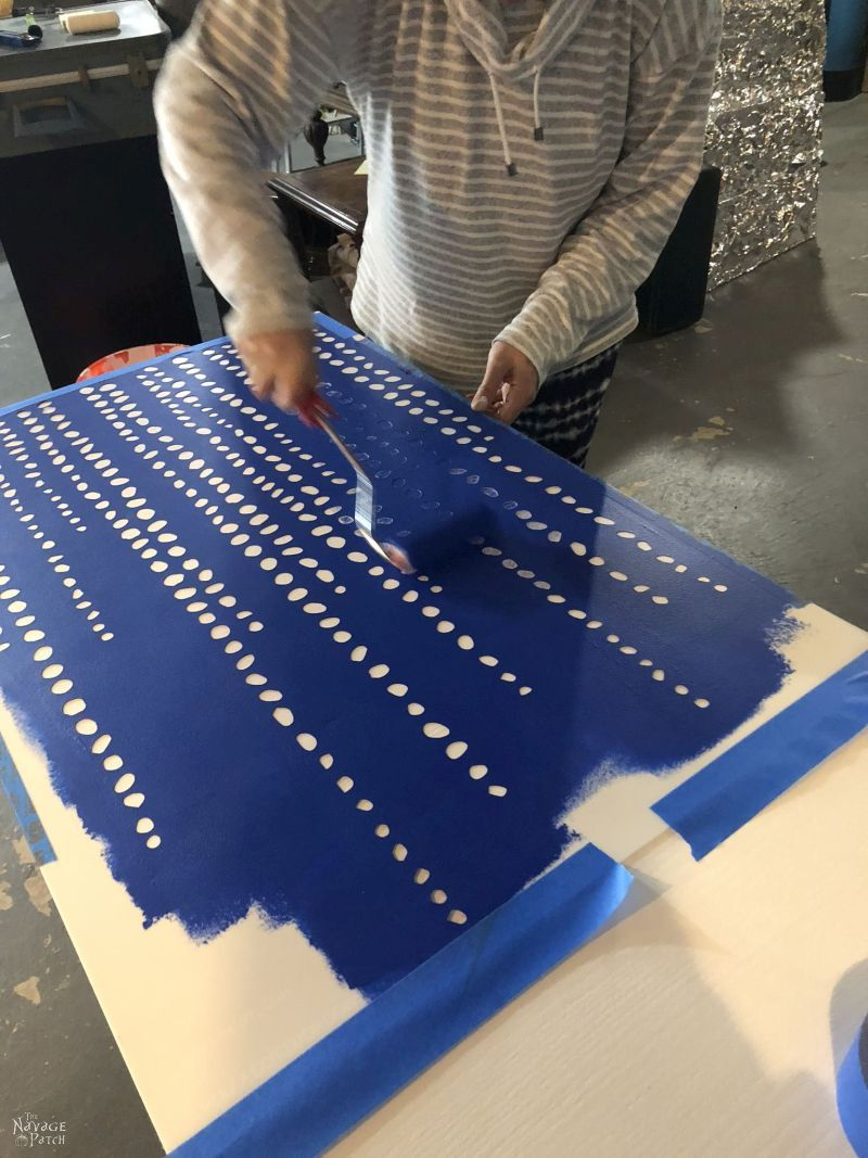 applying paint to a wall stencil