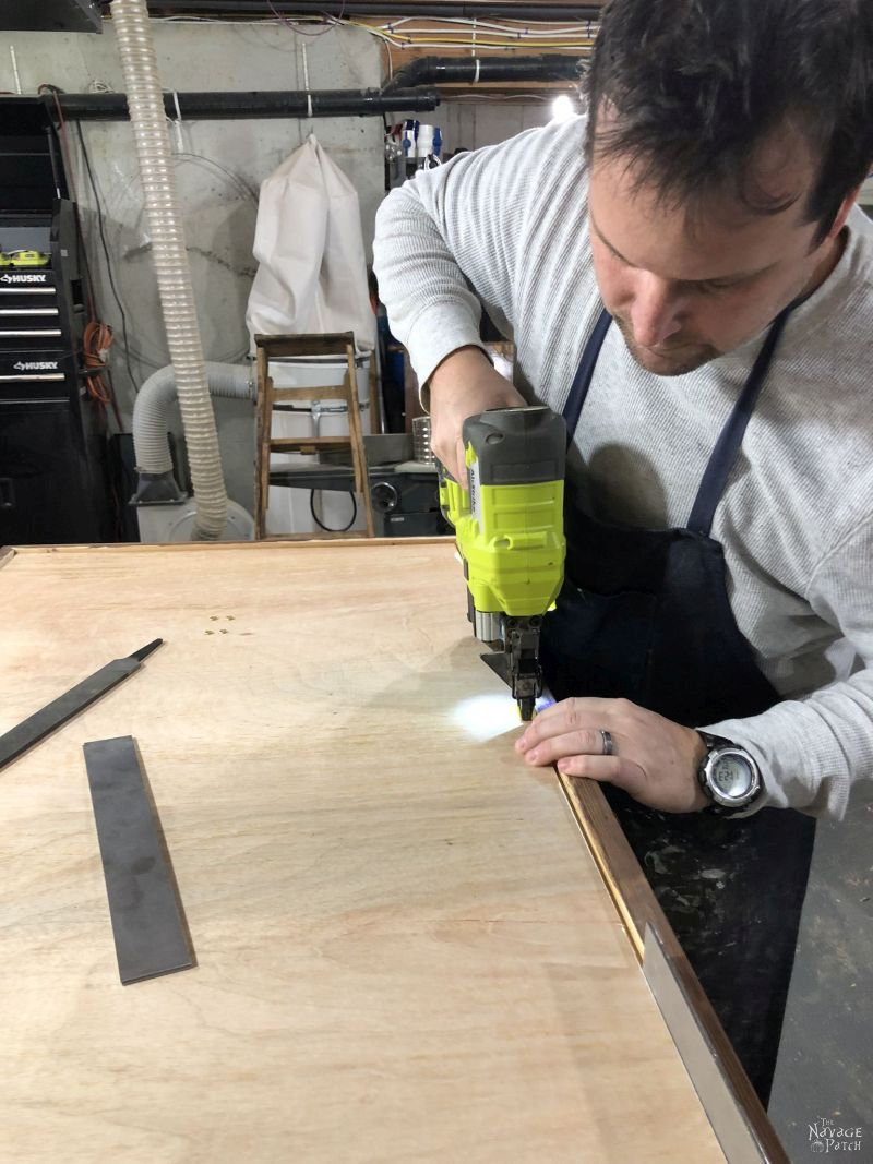 man using a brad nailer to install a frame backing