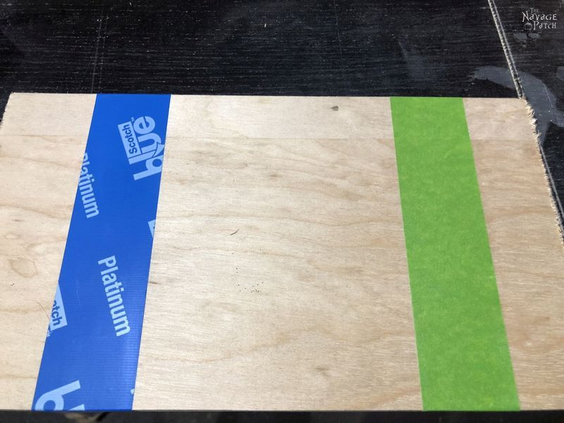 blue and green painter's tape on plywood