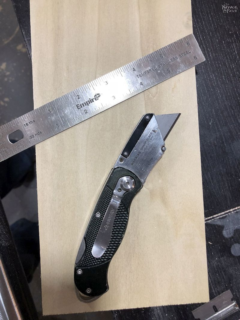 utility knife and ruler on a piece of plywood
