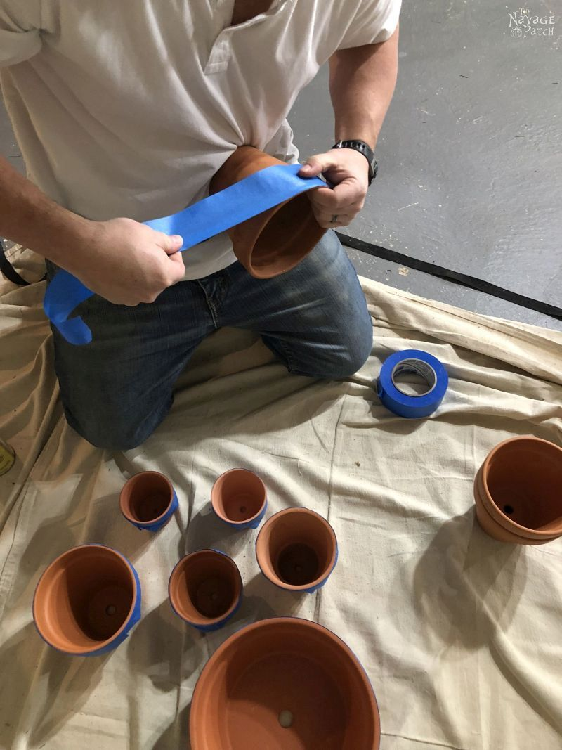 man wrapping blue tape around terra cotta pots